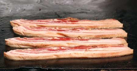 sizzle: An outdoor vendor cooks thick slices of bacon on a hot plate