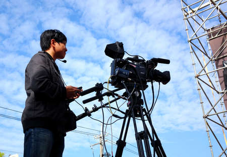 filming: LUJHU, TAIWAN -- DECEMBER 12, 2015: A professional camera man films the stage performances at the Lujhu Tomato Festival. Editorial
