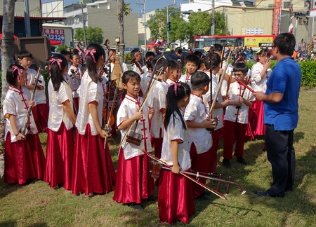 pipa: LUJHU, TAIWAN -- DECEMBER 12, 2015: A childrens orchestra for traditional Chinese music waits for their performance at the 2015 Lujhu Tomato Festival.