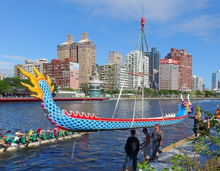 lowers: KAOHSIUNG, TAIWAN -- MAY 27, 2016: A crane lowers a dragon boat into the Love River in preparation for the upcoming Dragon Boat Festival.