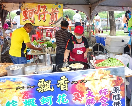 cook griddle: KAOHSIUNG, TAIWAN -- JUNE 9, 2016: An outdoor food stall prepares oyster omelets, a popular Taiwanese street food.