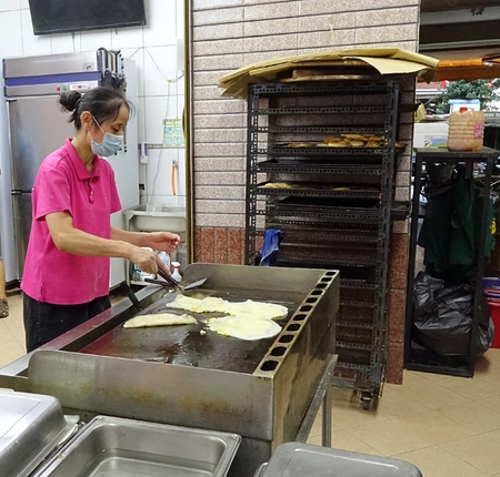 scallions: KAOHSIUNG, TAIWAN -- JUNE 9, 2016: A female chef at a traditional Chinese breakfast shop prepares fried pancakes with egg and scallions.