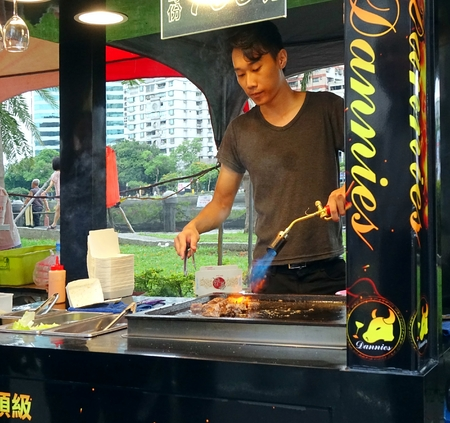 blowtorch: KAOHSIUNG, TAIWAN -- JUNE 9, 2016: A young male chef sears pieces of steak with a blowtorch at an outdoor food stall.
