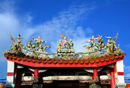 A Chinese temple with colorful decorations of mythological warriors Stock Photo