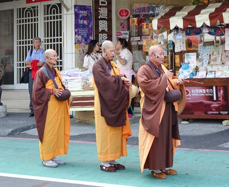 folk festival: KAOHSIUNG, TAIWAN -- OCTOBER 15, 2016: Three Buddhist monks prepare to chant scriptures during the yearly Wannian Folk Festival. Editorial