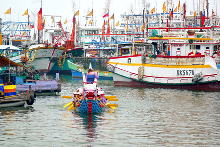 LINYUAN, TAIWAN -- MAY 28, 2017: A dragon boat team has just finished its race. In the back are fishing vessels anchored in the Zhongyun Fishing Port. Editorial