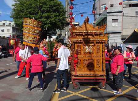 KAOHSIUNG, TAIWAN -- JUNE 10 , 2017: Religious devotees push a palanquin with intricate wood carvings during a religious ceremony.