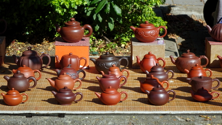 An outdoor vendor sells teapots made from characteristic red clay