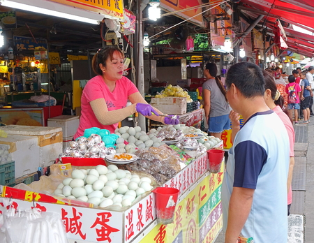 PINGTUNG, TAIWAN -- JULY 6 , 2017: A market vendor offers samples of salted duck eggs, a local specialty, to prospective customers.