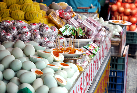 PINGTUNG, TAIWAN -- JULY 6 , 2017: A market stall sells local specialties such as salted duck eggs and preserved eggs and offers samples for tasting.