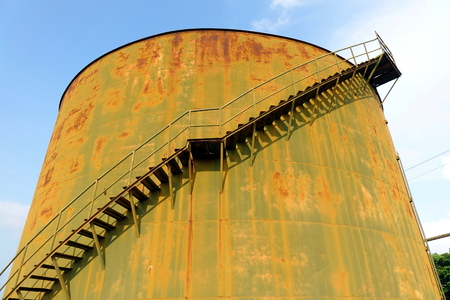 abandoned factory: A large rusting storage tank at a vintage industrial facility Stock Photo