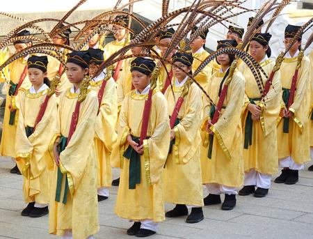高雄、台湾--9 月28日、2017: 黄色のローブの若い学生は、教師の日に開催される年次孔子儀式の間に孔雀の羽を運びます。