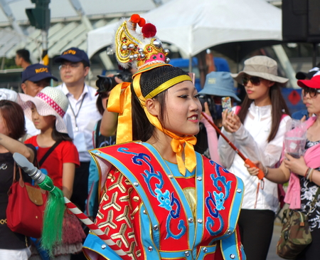 KAOHSIUNG, TAIWAN -- OCTOBER 1, 2017: A young woman dressed in a festive native costume joins the parade at the opening of the 2017 Ecomobility Festival. Editorial