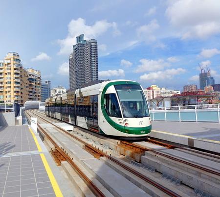 KAOHSIUNG, TAIWAN - 7 AUGUSTUS, 2017: Een trein van het nieuwe lightrailsysteem trekt in de Ware Liefdepijlerstation. Op de achtergrond zie je de skyline van de stad.