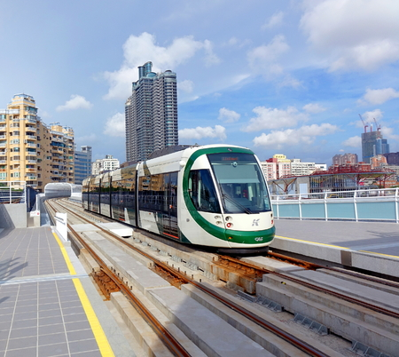 KAOHSIUNG, TAIWAN -- AUGUST 7, 2017: A train of the new light rail system pulls into the True Love Pier station. In the background you can see the city skyline. Publikacyjne