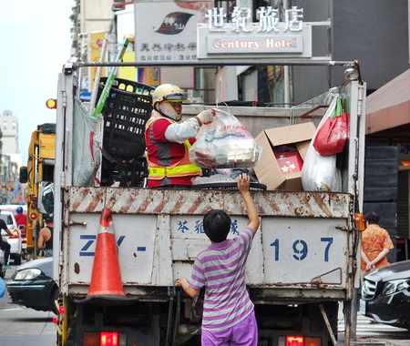 KAOHSIUNG, TAIWAN -- AUGUST 7, 2017: A woman passes a bag to a worker on a truck that collects recyclable materials.