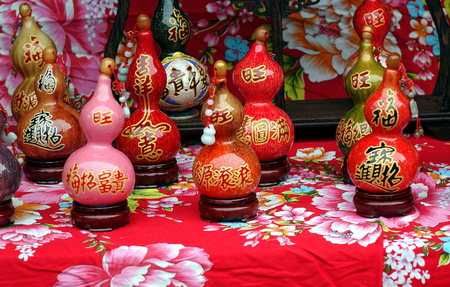 KAOHSIUNG, TAIWAN -- FEBRUARY 16, 2018: An outdoor vendor sells small dried gourds that are painted and varnished and decorated with Buddhist scriptures.