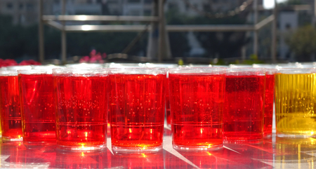 Glasses filled with sparkling red liquid in the morning sun