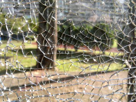 A view into garden through a broken glass window 스톡 콘텐츠