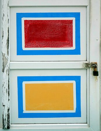 An old wooden door with red amd yellow painted rectangles Reklamní fotografie