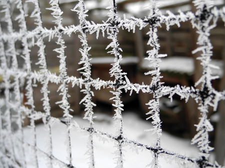 Winter white icy drizzle on the grid hanging on a wooden post