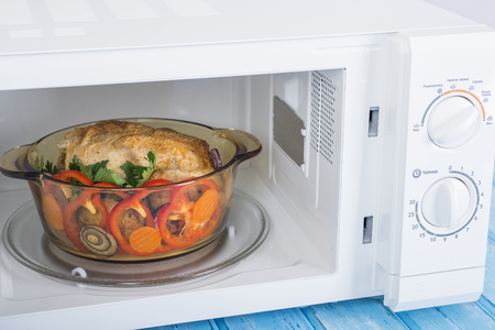 Appliances. A new white microwave oven, on a blue wooden surface for heating food