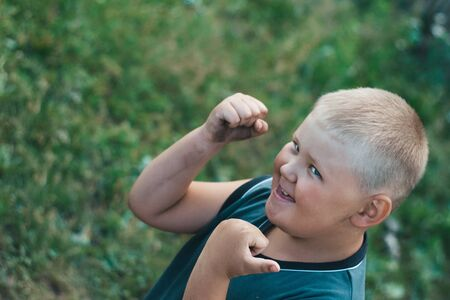 Fat dirty boy rejoices and dances in nature. The boy rejoices in victory in a street fight. A scruffy overweight boy of preschool