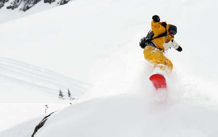 freeride: Yellow man snowboarder riding freeride and jumping high, splashing snow