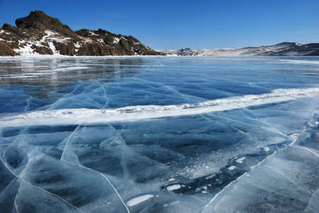 frozen lake: Surface of transparent fissured black ice of The Baikal Lake in winter Stock Photo
