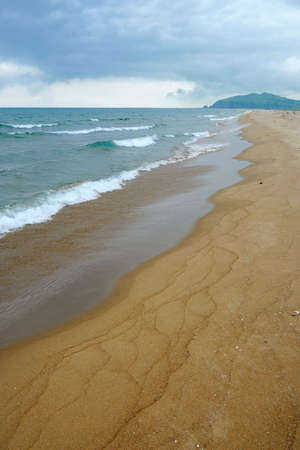 Sand beach view with wavy green sea and cloudy sky photo