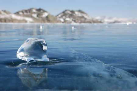 Transparent piece of ice on the mirrored surface of frozen lake. Low depth-in view. photo