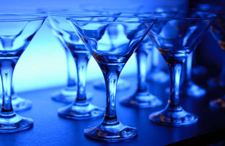 Wineglasses arranged in rows on the table in blue light photo