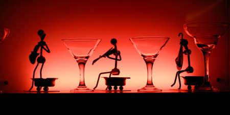 Wineglasses and statuettes of funny musicians on the table in red light photo