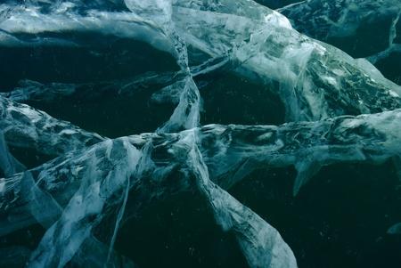 Black cracked ice background. Surface of frozen lake. photo