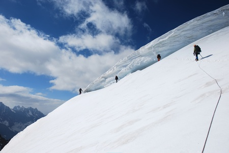 crevasse: Group of mountaineers climbing up the glacier slope near the crevasse
