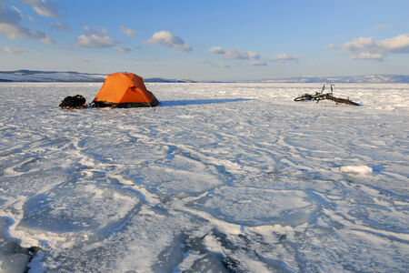 wintersport: Bicycle tourists' winter camp – orange tent and bikes on the surface of frozen lake in morning light