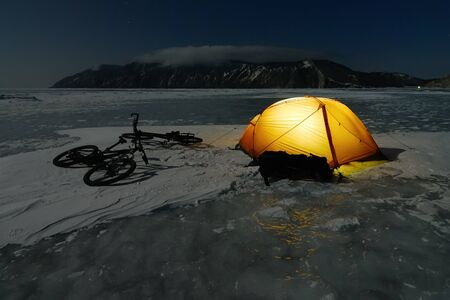 wintersport: Bicycle tourists' winter camp – orange tent and bikes on the surface of frozen lake. Night scene