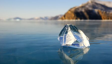 Piece of ice on the surface of frozen lake Baikal. Close-up view. photo