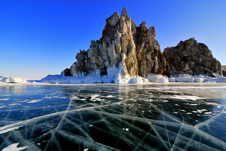 Surface of frozen lake Baikal. Cliff rock with icicles. photo