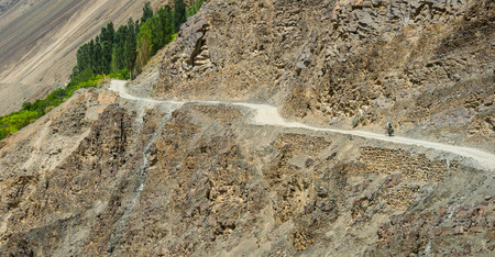 road cycling: Bicycle tourist riding by the winding steep bumpy mountain road Stock Photo
