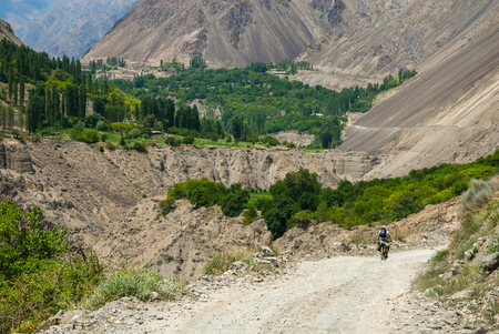 bumpy: Bicycle tourist riding down the bumpy and winding mountain road in the valley Stock Photo