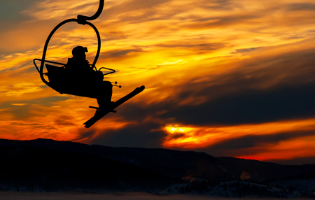 lonesome: Silhouette of lonesome skier climbing up by the chair lift in sunrise