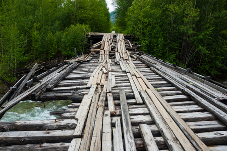 bumpy road: Old destroyed wooden bridge on the bumpy road in Russian backwoods