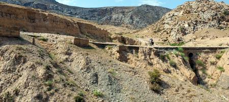 bumpy: Bicycle tourist riding down the bumpy mountain road