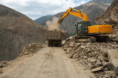 dumptruck: Dump-truck and excavator on roadwork. Repairing of mountain road.