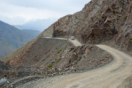 Small car on the steep and shallow dangerous mountain road