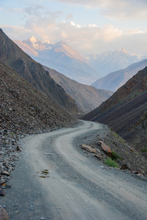 unpaved road: Dangerous steep and shallow unpaved road in mountains in the evening light