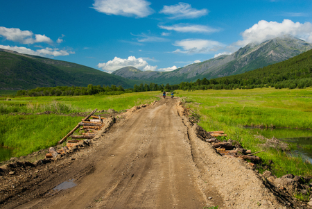bumpy: Two bicycle tourists riding by the bumpy gravel road throw the swamp to mountains Stock Photo