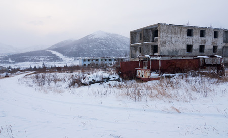 Abandoned settlement with decayed buildings and old destroyed bus in Kolyma winter view Stock Photo