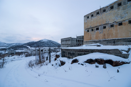 Exterior of old decayed abandoned prison in Kolyma in evening light